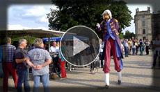 Der barock gekleidete Stelzenläufer unterhält die Gäste mit Hofgeschichten