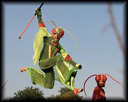 Scheinbar schwerelos fliegt der Artist im Grashüpfer Kostüm auf Springstelzen durch die Luft.