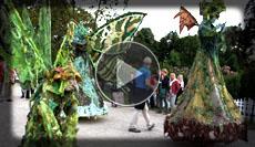 Stelzenläufer in Kostümen die an Wald und Waldbewohner erinnern