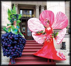Zwei attraktive Damen begrüßen lächelnd die Gäste in einem Weintrauben- und Kirschblütenkostüm