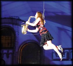 In der Luft schwebend spielt die Solo Saxophonistin ein umfassendes Musikrepertoire