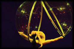 Luftakrobatin in einer Kugel aus Plexiglas schwebt wie ein Vogel durch die Luft